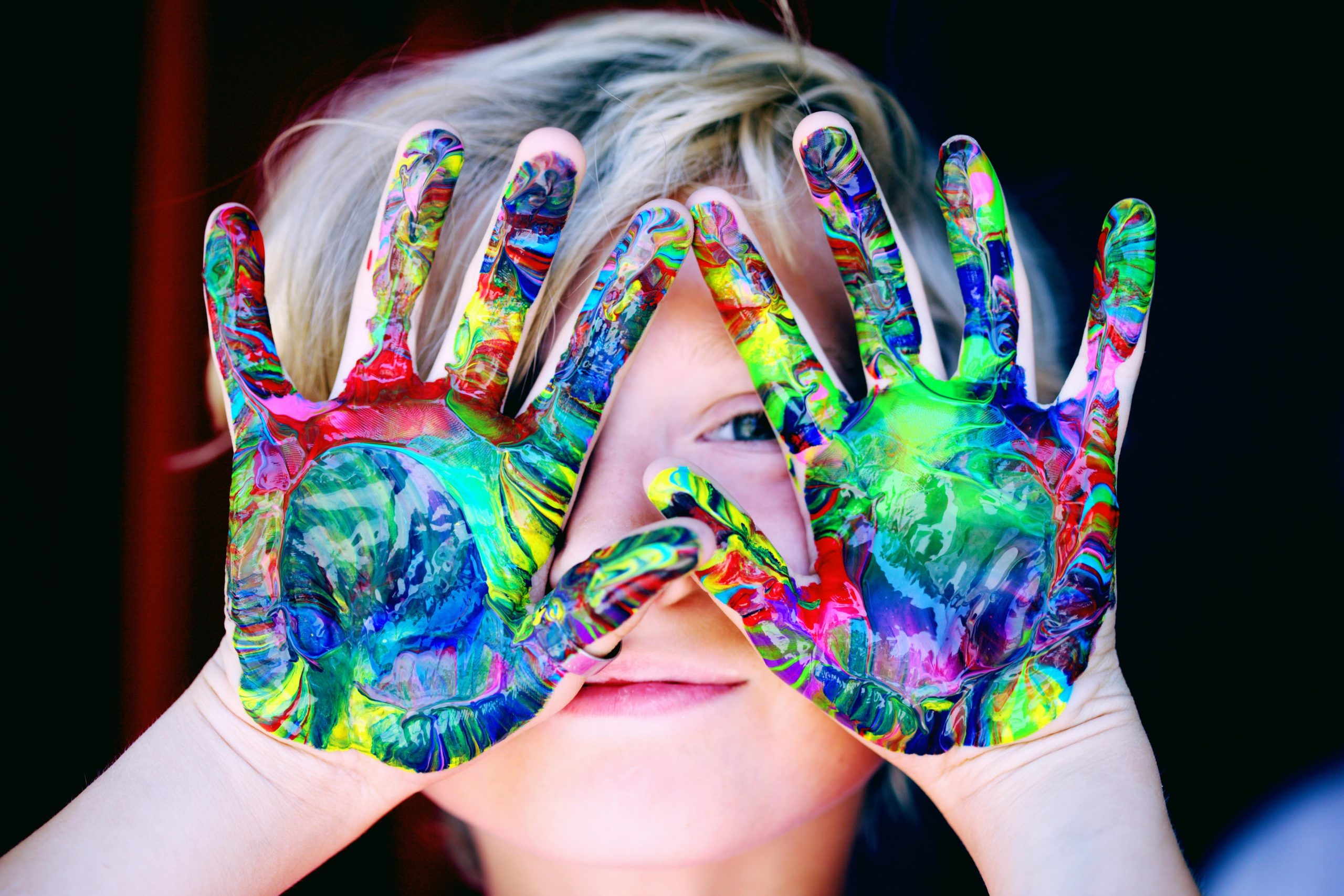stress management kid with rainbow paint on hands